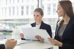 女实业家谈论在文件在办公室自助食堂 库存图片