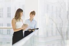 女实业家谈论在片剂个人计算机,当支持栏杆在办公室时 免版税库存图片