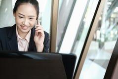 女实业家谈话在手机在办公室 年轻女性en 免版税库存图片
