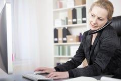女实业家谈话在键入在计算机上的电话 免版税库存照片