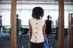 女实业家输入的会议室背面图见面的 库存照片