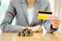 女实业家递与信用卡和许多硬币在专栏 免版税库存照片
