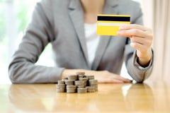 女实业家递与信用卡和许多硬币 免版税库存照片