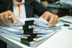女实业家递工作在堆飞翅的文件 图库摄影