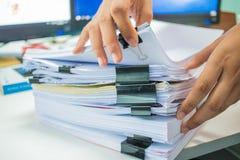 女实业家递工作在堆飞翅的文件 免版税库存照片