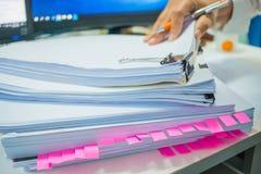 女实业家递工作在堆飞翅的文件 库存照片