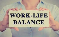 女实业家递拿着与工作生活平衡消息的卡片标志 免版税库存照片