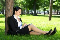女实业家逗人喜爱的公园工作 免版税库存图片