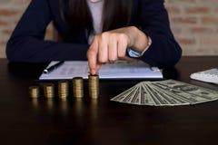 女实业家采摘在桌上的硬币,计数金钱 事务 库存图片