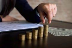 女实业家采摘在桌上的硬币,计数金钱 到达天空的企业概念金黄回归键所有权 免版税库存照片