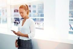 年轻女实业家集中了文字正文消息她的手机,当站立在现代办公室内部时, 免版税库存照片