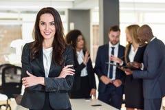 女实业家领导在有买卖人workin的现代办公室 库存图片