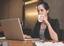 女实业家饮用水,当工作时 库存图片