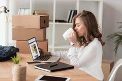 女实业家饮用的咖啡侧视图,当研究膝上型计算机时 图库摄影