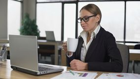 女实业家饮用的咖啡在办公室,有断裂,休息在被完成的工作以后 股票录像