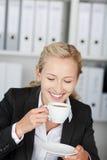 女实业家饮用的咖啡在办公室 免版税图库摄影