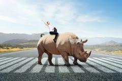 女实业家骑马犀牛 混合画法 库存照片