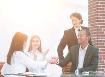 女实业家,握手,与满意的客户的密封的闭合值的成交的多种族伙伴 库存图片