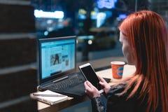 女实业家,研究在咖啡馆,举行智能手机在手上,笔,用途电话的膝上型计算机的女孩 : 在网上, 免版税库存照片