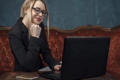 女实业家,衣服的愉快的妇女微笑使用工作的膝上型计算机的在葡萄酒内部 免版税库存照片