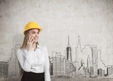 女实业家戴一顶黄色安全帽和谈话在她的智能手机,当站立在有城市全景的时一个混凝土墙附近 免版税图库摄影