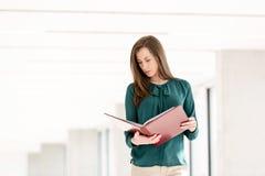 年轻女实业家读书文件在新的办公室 免版税库存照片