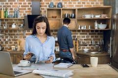 年轻女实业家读书杂志,当在家时工作 免版税库存照片