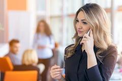 年轻女实业家画象在拿着她的机动性的办公室 免版税库存图片