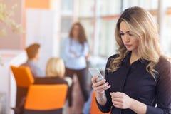 年轻女实业家画象在拿着她的机动性的办公室 免版税库存照片
