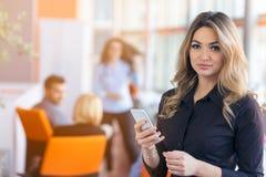 年轻女实业家画象在拿着她的机动性的办公室 库存图片