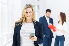 女实业家画象谈话在电话在办公室 免版税库存图片