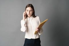 女实业家画象谈话在电话 一在灰色背景被隔绝 免版税图库摄影