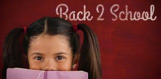 女小学生与书的覆盖物嘴的综合图象 库存图片