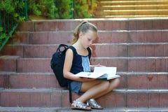 女小学生做在台阶的8岁家庭作业读书 免版税库存照片