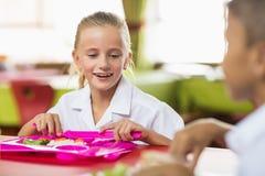 女小学生吃午餐在断裂时间在学校食堂 免版税库存图片