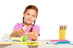 女小学生和她的手工制造origami玩具 免版税库存照片