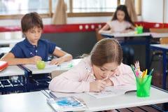 女小学生图画,当倾斜在书桌时 免版税库存照片