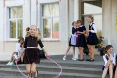 女小学生在绳索跳在学校前面的变动 库存照片