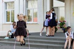 女小学生在绳索跳在学校前面的变动 库存图片