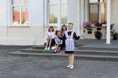女小学生在绳索跳在学校前面的变动 免版税库存图片