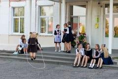女小学生在绳索跳在学校前面的变动 免版税图库摄影