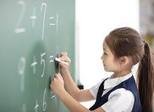 女小学生在黑板的文字答复 免版税库存照片
