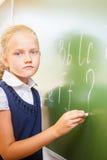 女小学生在黑板写与白垩的英语字母表 免版税库存照片