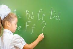 女小学生在黑板写与白垩的英语字母表 免版税库存图片
