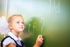 女小学生在黑板写与白垩的英语字母表 库存图片