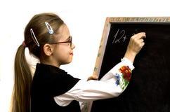 女小学生在黑板写了 免版税库存图片