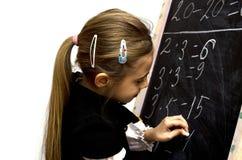 女小学生在黑板写了 库存照片