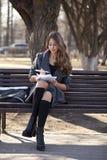 女小学生坐与一个笔记本的一条长凳在春天公园 免版税库存照片