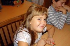 女小学生坐在书桌并且微笑 免版税库存照片