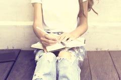 女小学生坐地板和在日志写了 免版税库存照片